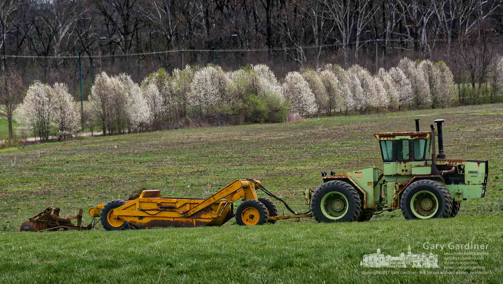 Wild pear tree blossoms line the roadway at the edge of the Braun Farm property where a heavy duty tractor sits waiting for warmer and drier weather to begin spring planting. My Final Photo for April 3, 2017.