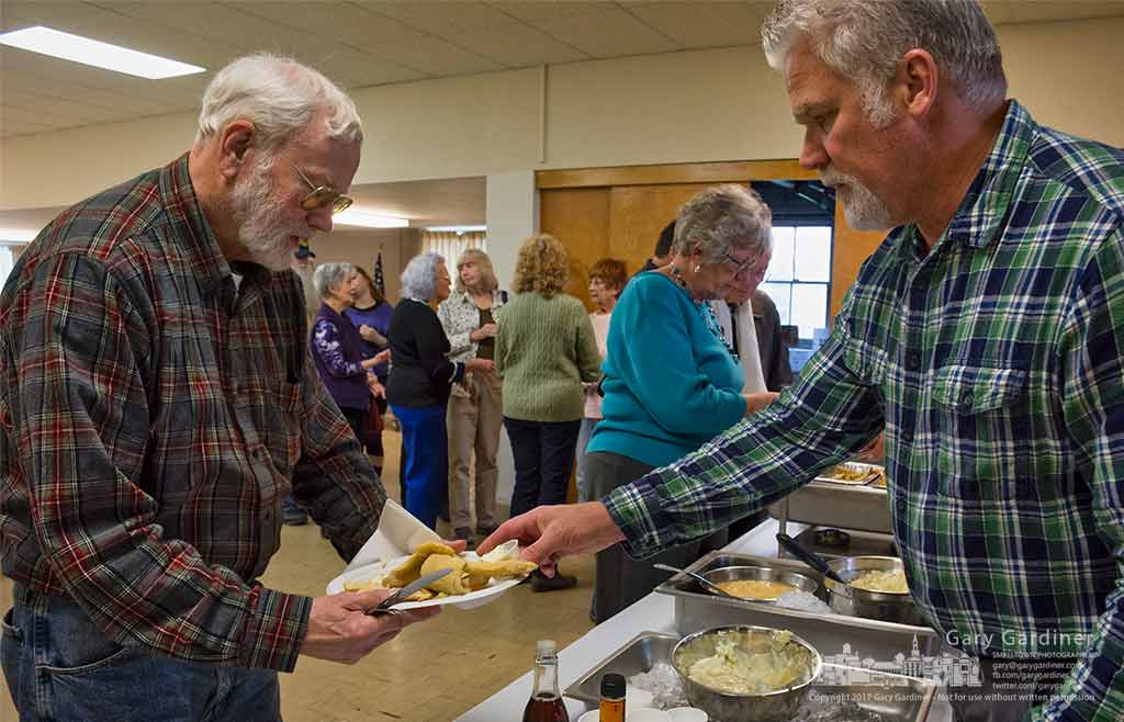 Diners receive their plates of fish and fries at the Blendon Masonic Temple all-you-can-eat dinner to benefit the Special Olympics. My Final Photo for April 7, 2017.