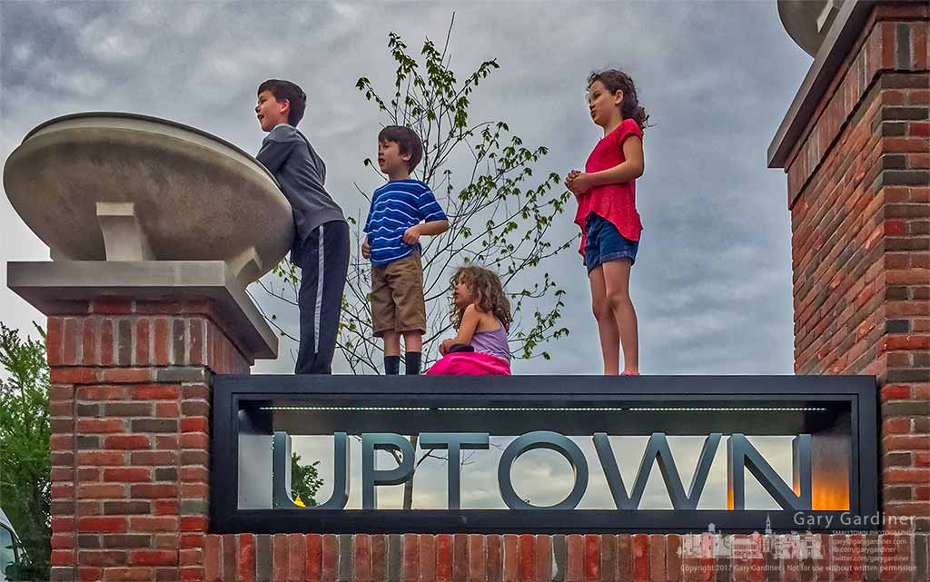 A group of kids watching dancers in front of Generations use the Uptown sign at City Hall for an unobstructed view of College Ave. My Final Photo for April 17, 2017.