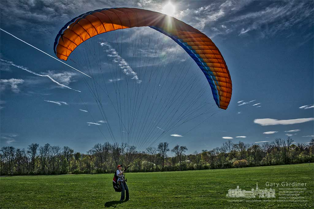 Kyle Gibney inflates his paraglider on the grassy fields of the sports complex to prepare it and him for an adventure trip this spring. My Final Photo for April 18, 2017.