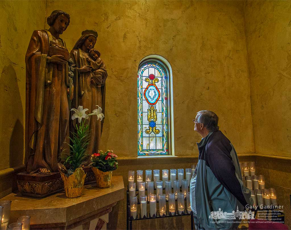 Ed Zgonc looks toward a stained glass window after lighting a candle at St. Paul Catholic Church for a friend whose father is having heart surgery. My Final Photo for May 3, 2017.