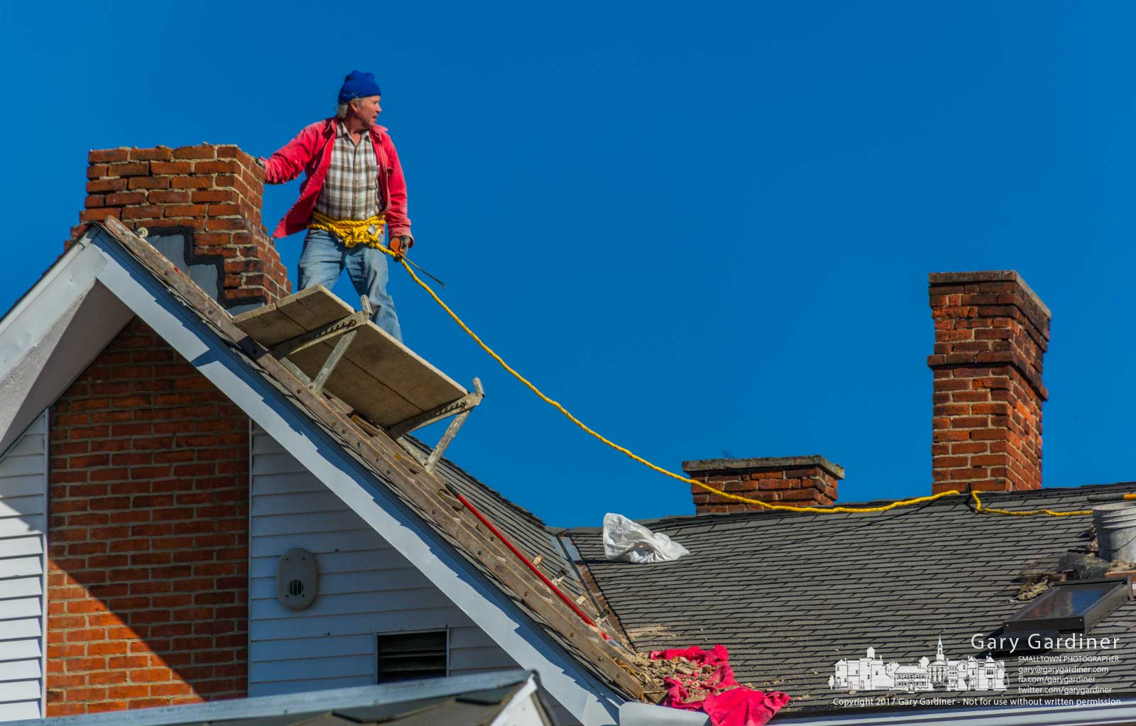 A brickmason surveys his position and movement on the roof of an East College house as he makes repairs to its chimneys. My Final Photo for Nov. 28, 2017.