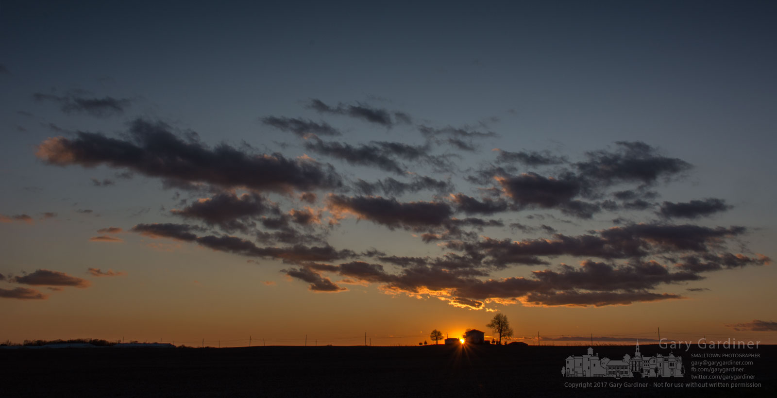 The sun sets behind a farmhouse on a ridgeline along a country road neat Hartford, Ohio. My Final Photo for Nov. 25, 2017.