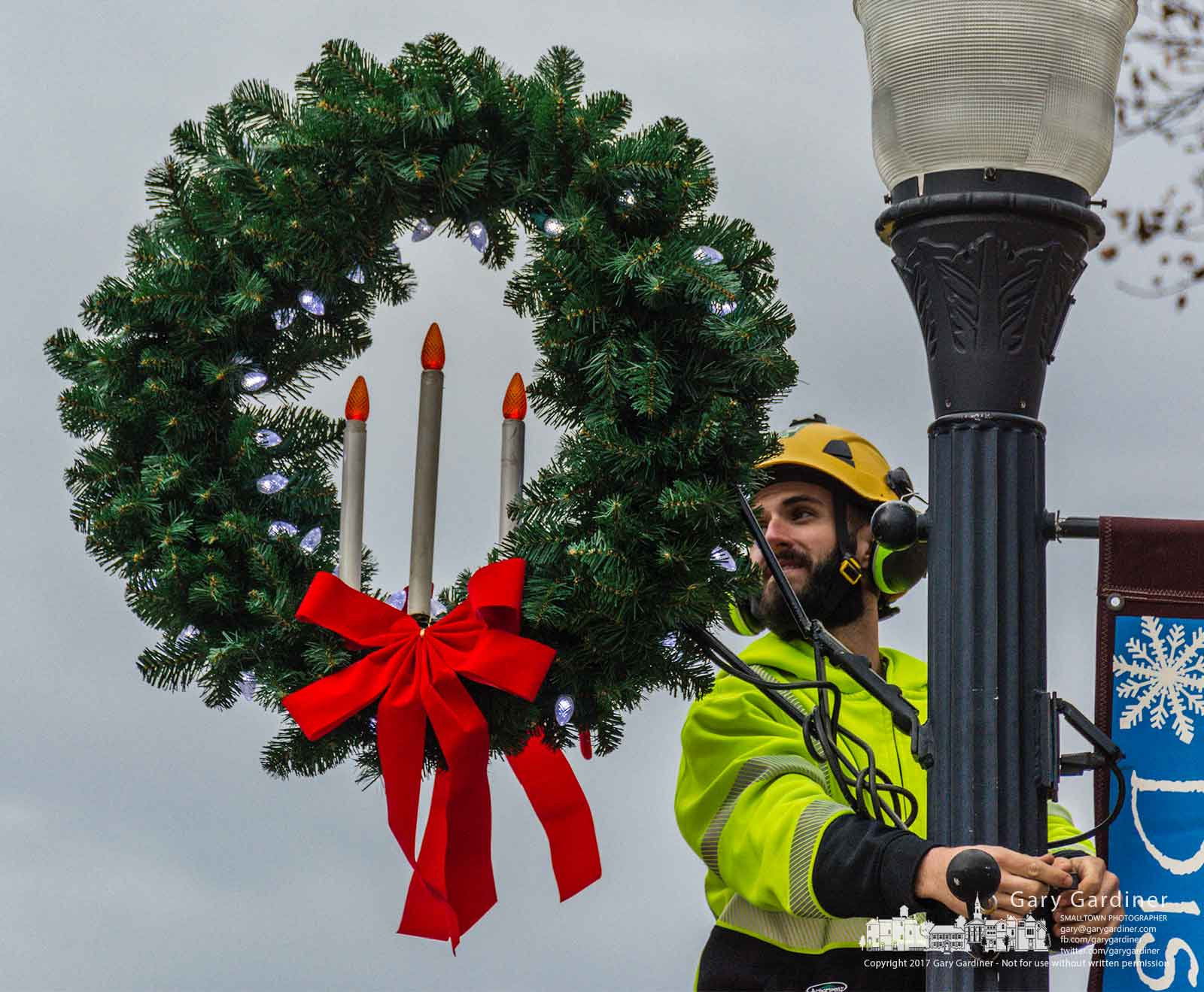 A city electric worker plugs in the lights wrapped into one of the wreaths being placed on street light poles in Uptown Westerville before Friday night's tree lighting. My Final Photo for Nov. 30, 2017.