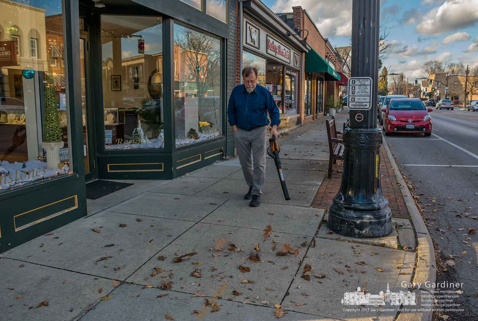 Jeweler Bill Morgan uses a battery-powered blower to clear leaves from inside and in front of his store in Uptown in what he says is continuing battle as the wind whips around the corner of his State and Main building. My Final Photo for Dec. 6, 2017.