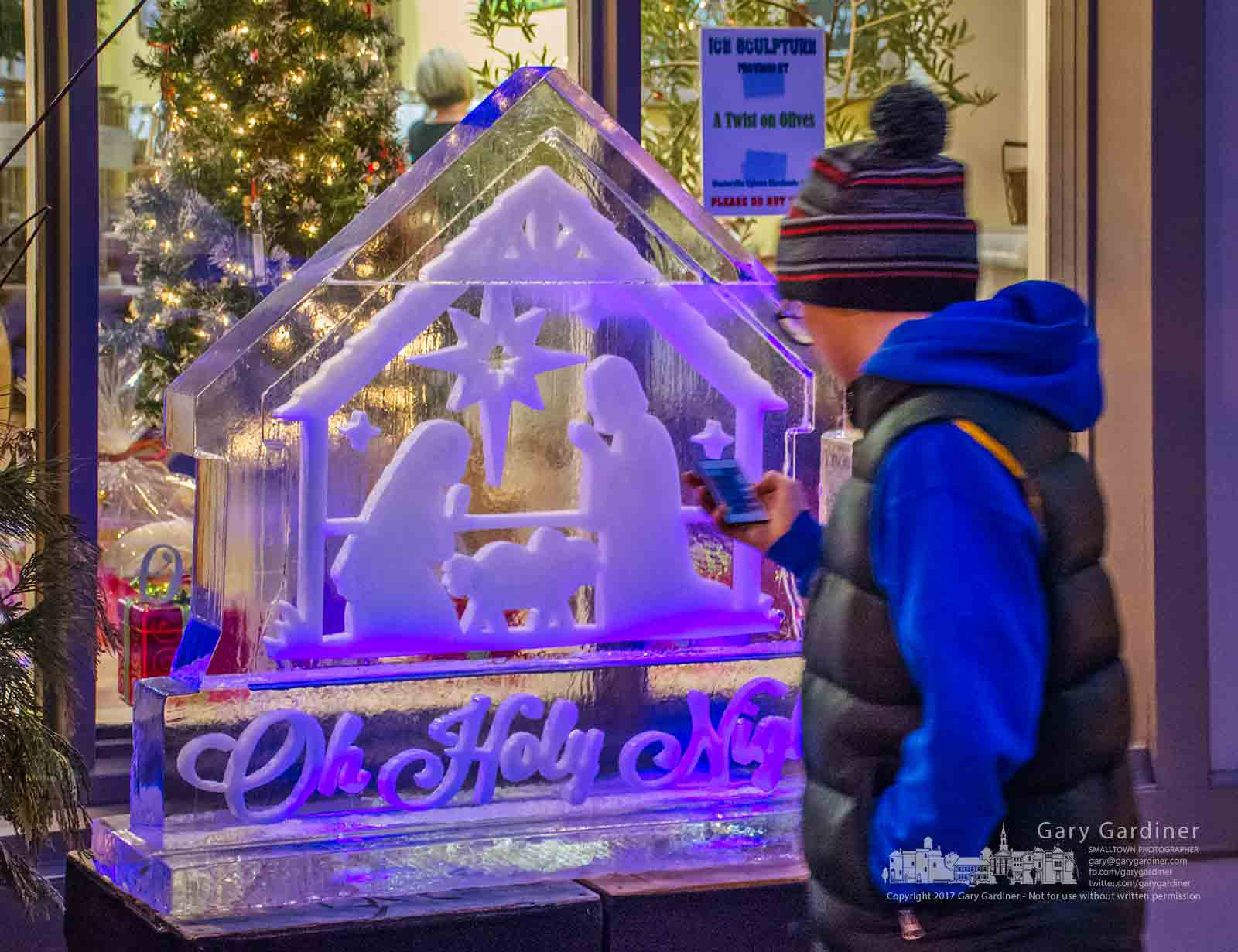 Nine-year-old Hayden uses a remote control to turn on lights beneath one of the ice sculptures installed on the sidewalk in Uptown Westerville Friday afternoon. My Final Photo for Dec. 15, 2017.