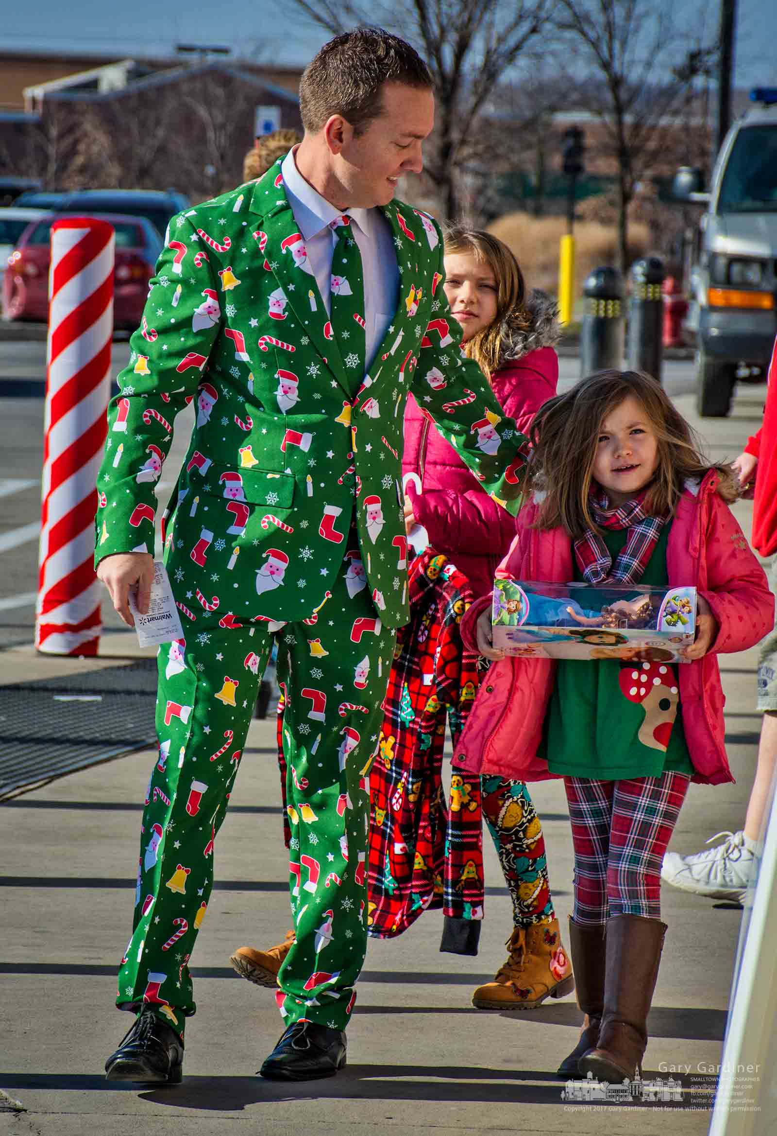 A father wearing the Christmas ugly sweater competition suit he will wear to a family gathering walks with his daughters to the Westerville Police W.A.R.M. collection boxes outside Walmart in Westerville. My Final Photo for Dec. 16, 2017.