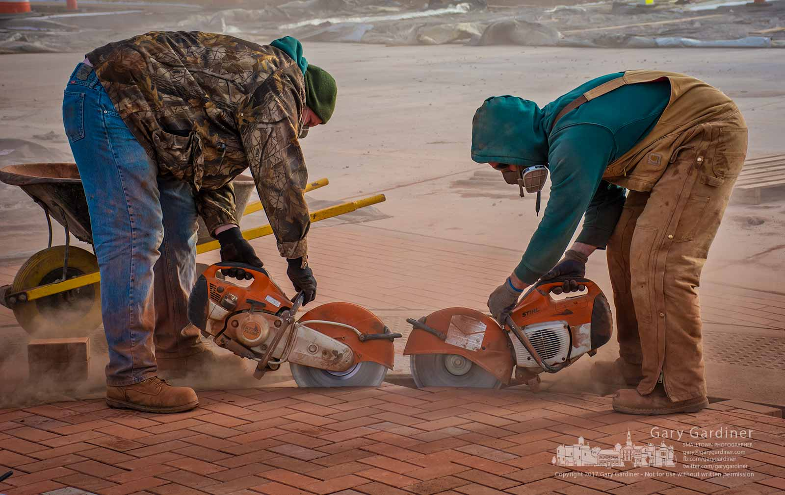 A pair of bricklayers cutting pavers reach the middle of an entrance built into the roadway across from the entrance to the Renaissance Hotel on Altair Parkway. My Final Photo for Dec. 14, 2017.