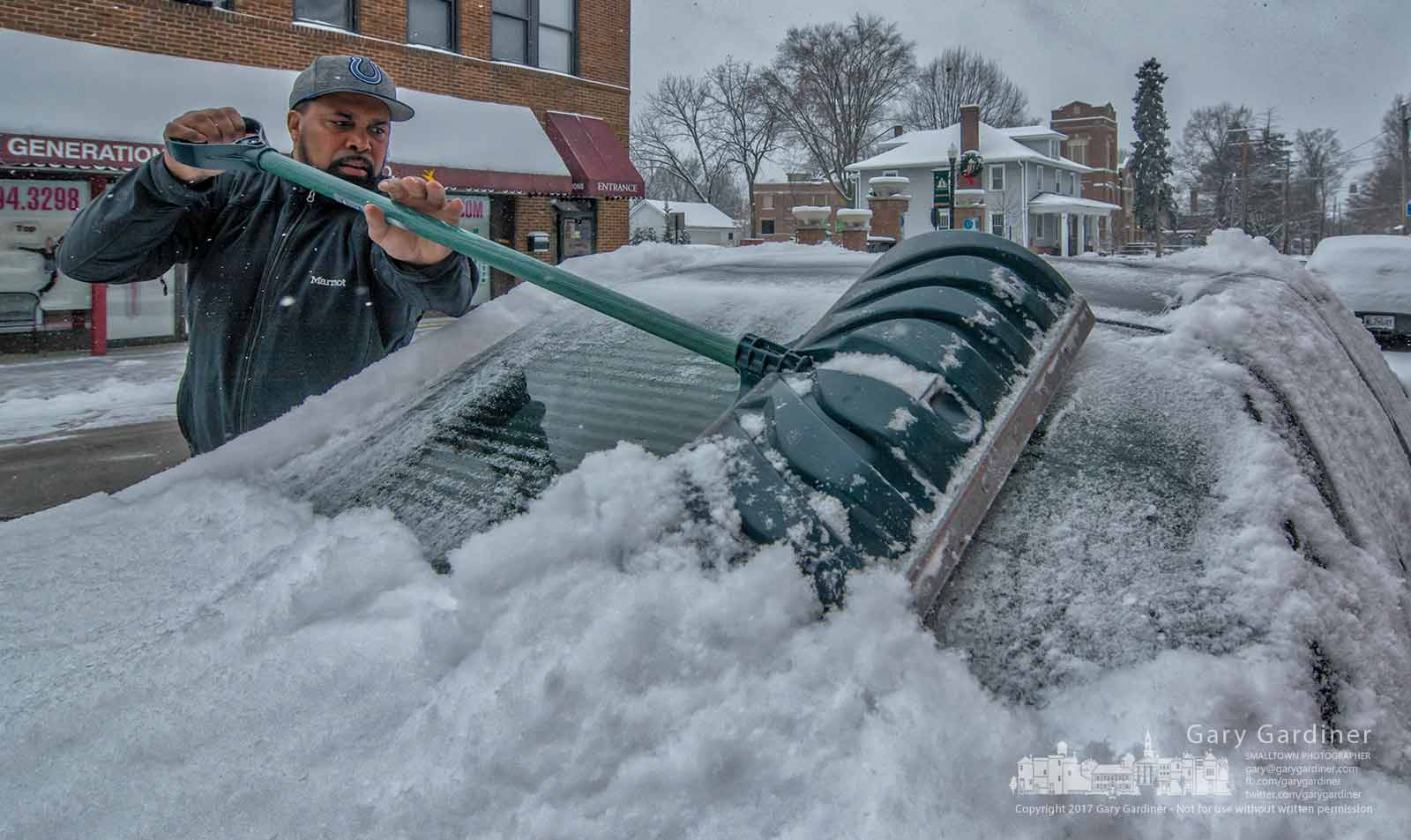 A driver uses a snow shovel to scrape the overnight snow from his car before heading on his day's trips from Uptown Westerville. My Final Photo for Dec. 30, 2017.