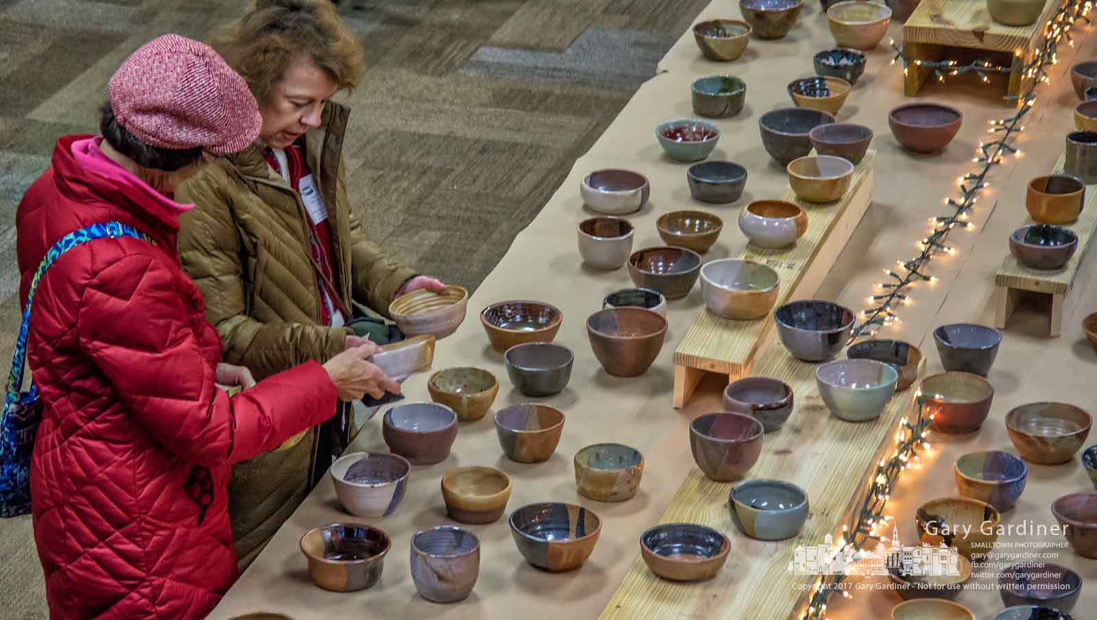 Two women sort through a table of soup bowls fashioned by Columbus Academy students for the Soup for Shelter fundraiser at Otterbein University for Westerville Habitat Partnership. My Final Photo for Dec. 8, 2017.