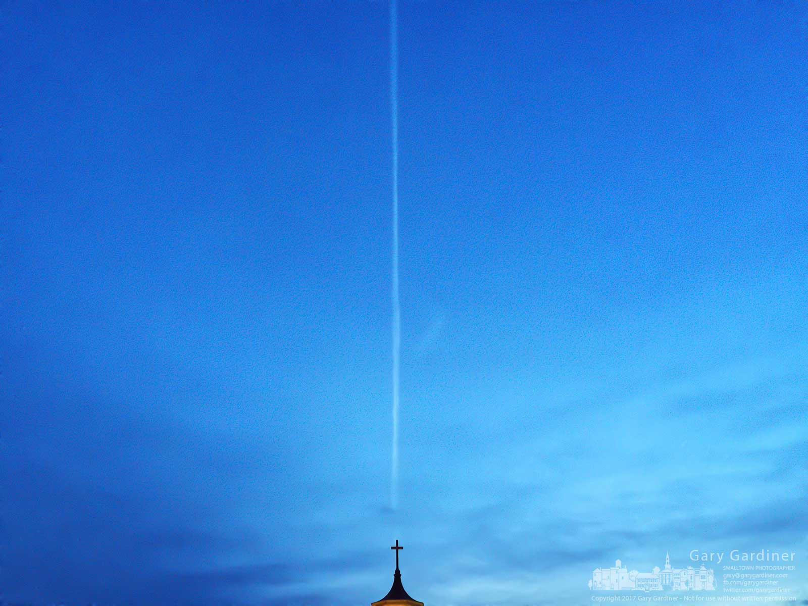 An early morning flight creates a contrail behind the cross atop the old steeple for St. Paul the Apostle Catholic Church in Westerville. My Final Photo for Dec. 17, 2017.