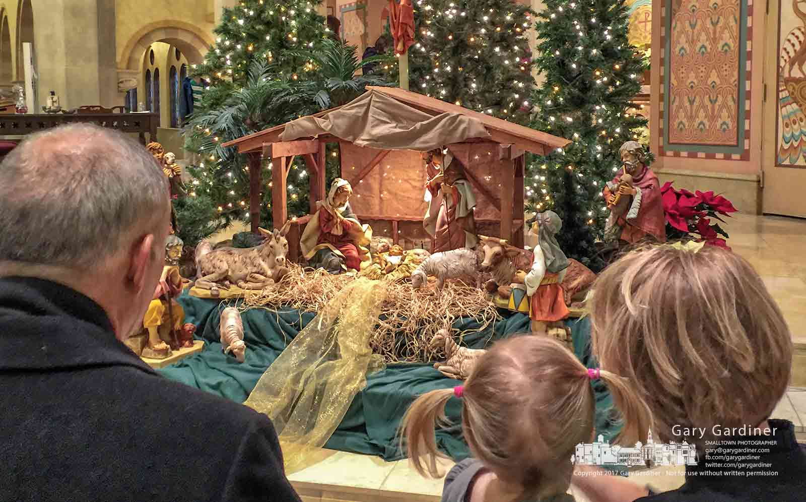 A family examines the nativity scene adjacent to the altar after the Christmas Eve morning Mass at St. Paul Catholic Church in Westerville. My Final Photo for Dec. 24, 2017.