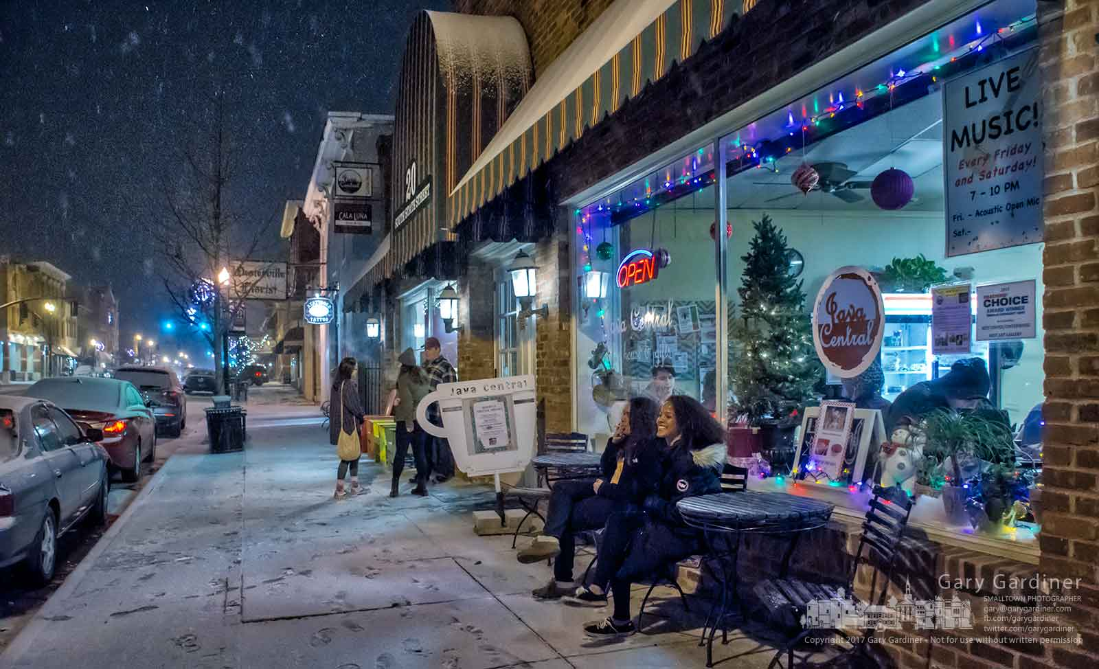 A pair of customers take a break outside Java Central as the snow begins to fall in Uptown Westerville. My Final Photo for Dec. 29, 2017.
