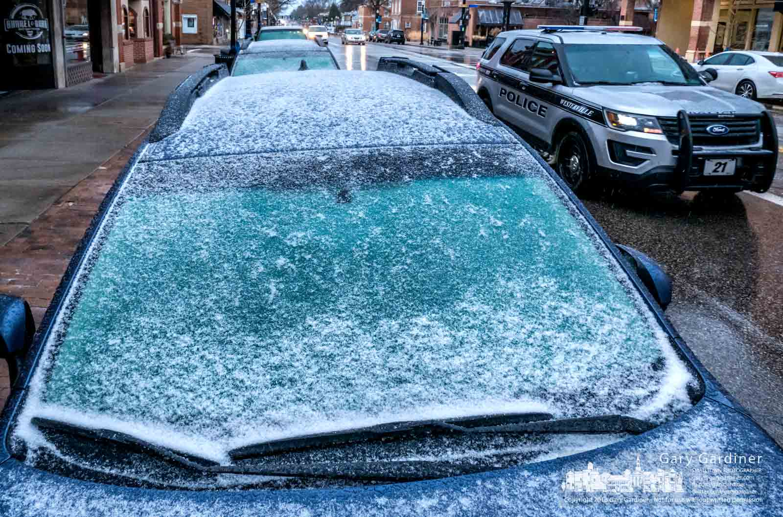 A Westerville Police officer passes a parked car in Uptown with its windshield covered in rain, sleet, and snow in later afternoon as the winter storm moved across Central Ohio. My Final Photo for Jan. 12, 2018.