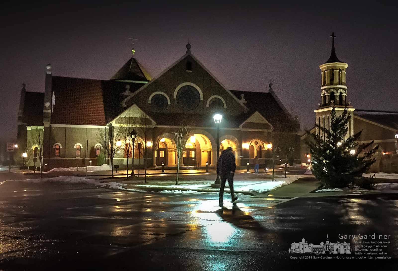 A parishioner steps across pavement west from melting snow as he makes his way to the early Sunday Mass at St. Paul the Apostle Catholic Church in Westerville, Ohio. My Final Photo for Jan. 21, 2018.