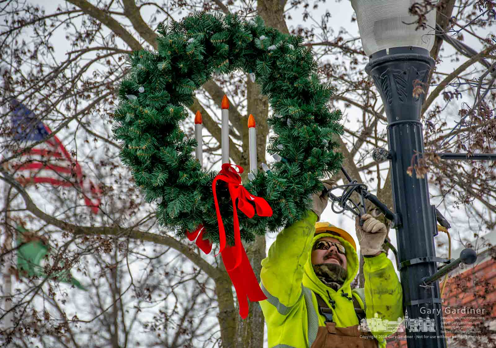 A city service worker removes the last decorative wreath from Winter Street in Uptown Westerville marking the end of street light decorations for the Christmas season. My Final Photo for Jan. 3, 2018.