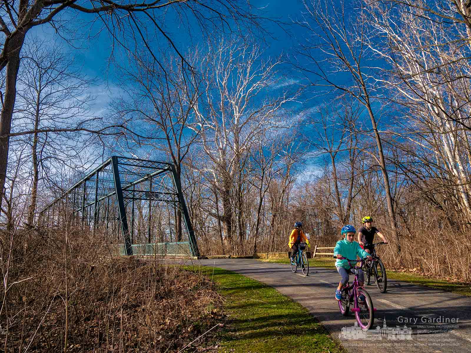 A family rides along the bike path near the steel bridge crossing Alum Creek as they enjoy a warm February afternoon together. My Final Photo for Feb. 27, 2018.