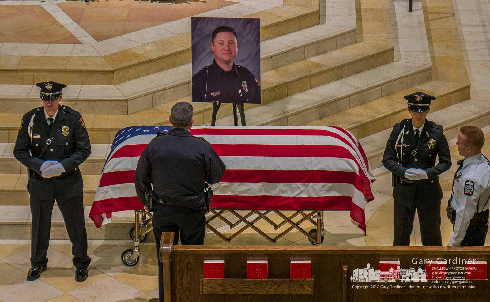 A police officer pauses with his head lowered as he passes the casket of Westerville Police Officer Eric Joerning who was killed on duty last week. My Final Photo for Feb. 16, 2018.