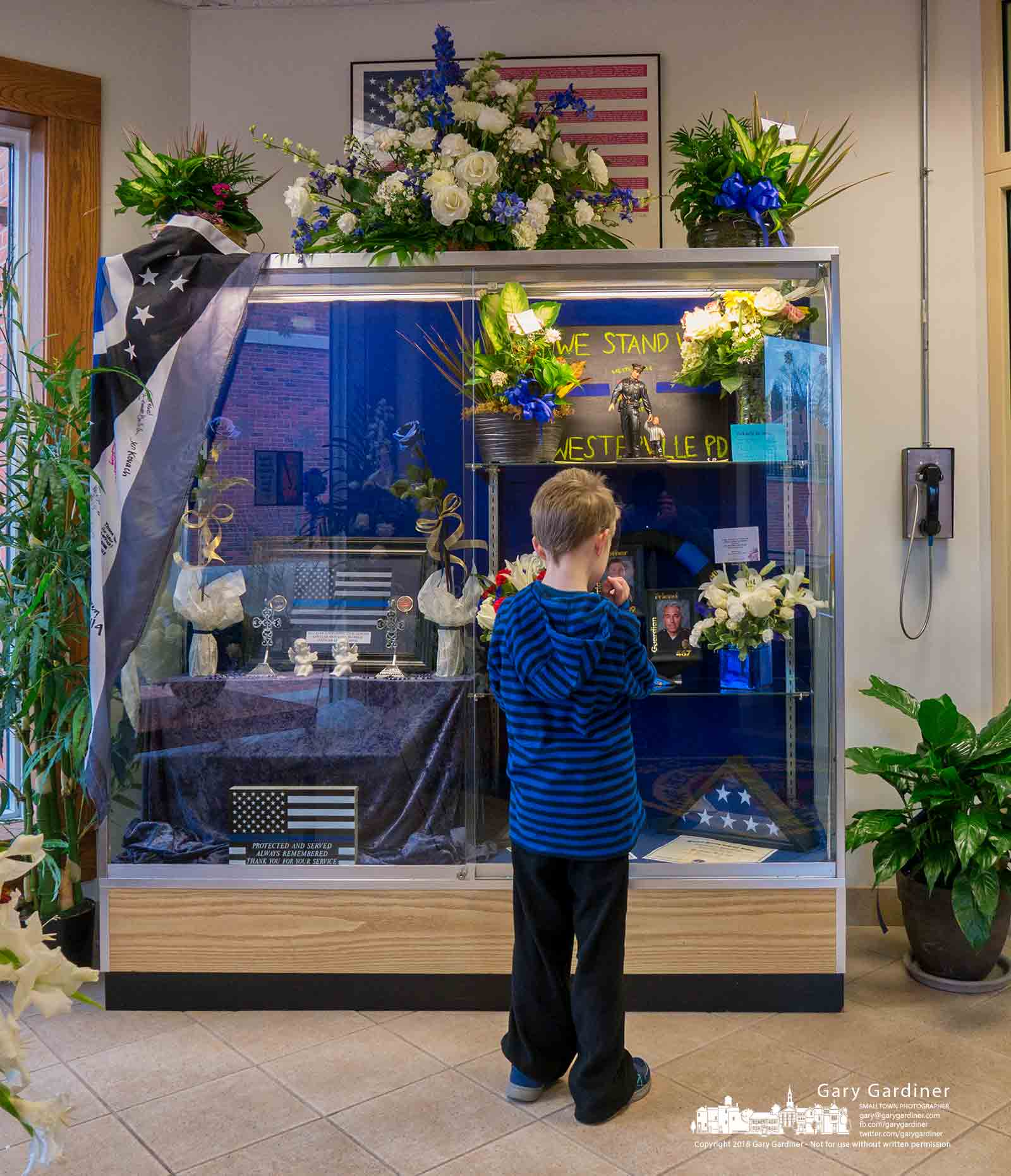 A young boy stands in front of the lobby memorial for Westerville Police Officers Eric Joering and Tony Morelli where two flags from the Capitol Police that flew over the US Capitol Building were added. My Final Photo for Feb. 21, 2018.