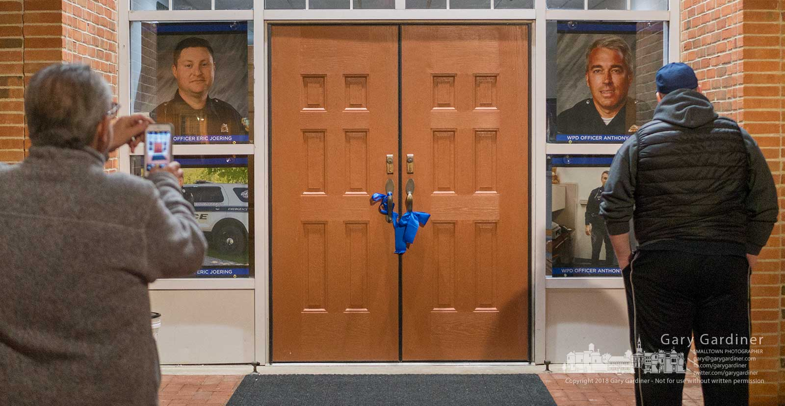 Mourners pause at the entrance to city hall where photos of Westerville Police Officers Eric Joering and Anthony Morelli are displayed. The two officers were killed Saturday. My Final Photo for Feb. 11, 2018.