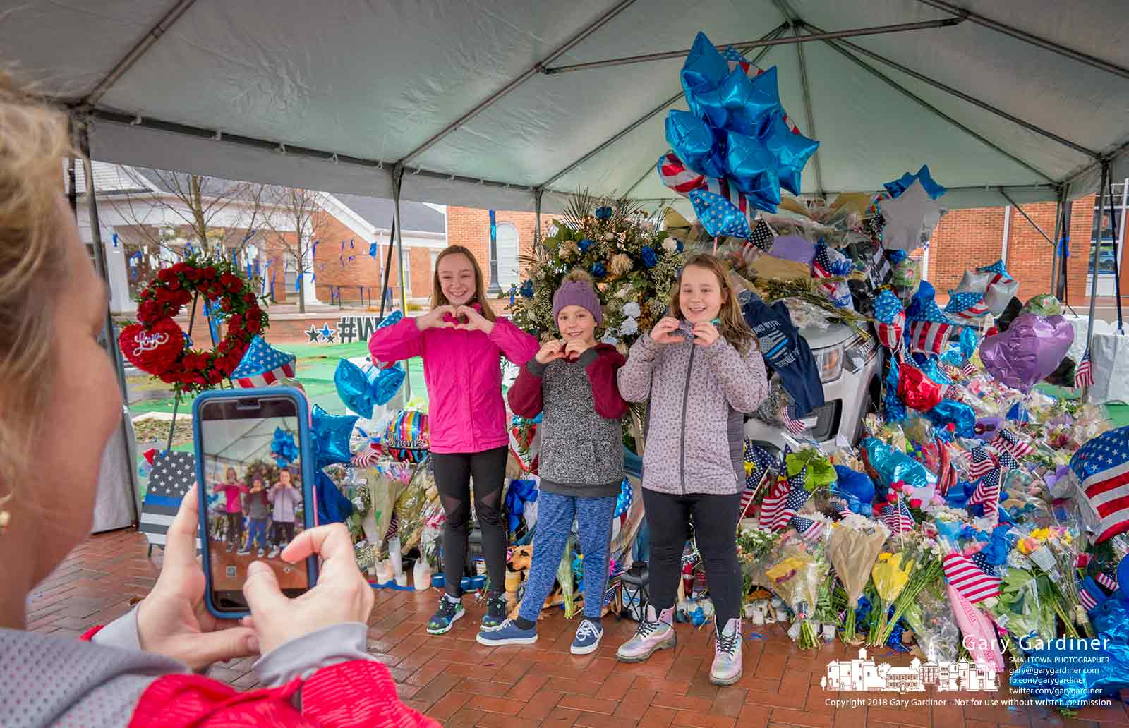 Three children pose with heart-shaped hands for a photo in front of the memorial for Westerville Police Officers Tony Morelli and Eric Joering at city hall. My Final Photo for Feb. 19, 2018.