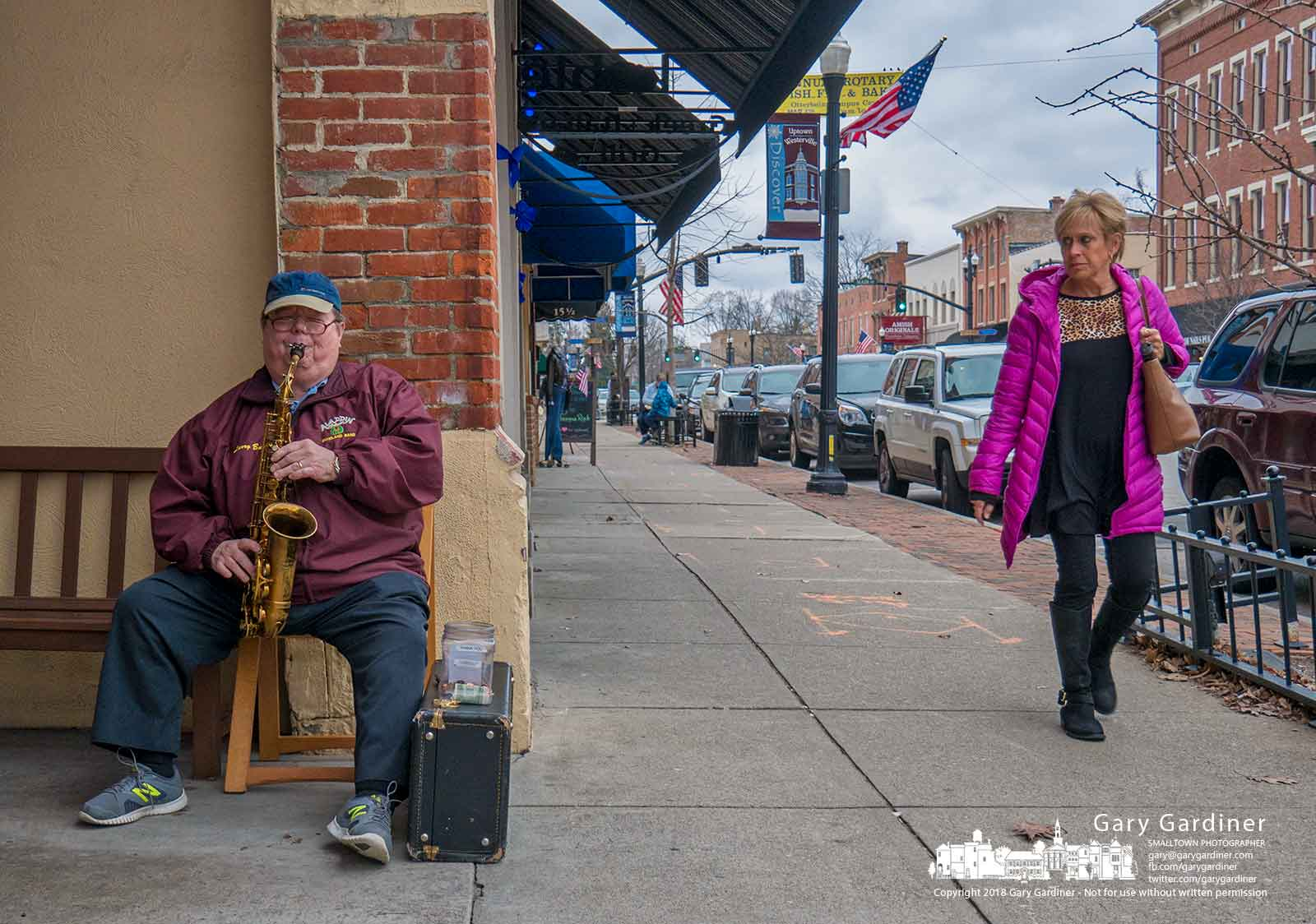 A saxophone busker performs to a single listener turning as she passes him in front of Graeters in Uptown Westerville on a warm winter day. My Final Photo for Feb. 28, 2018.