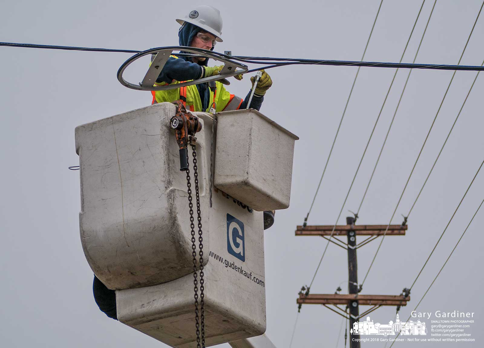 A linesman clears away sections of cabling attached to old utility poles at Schrock and Cleveland where the intersection and roadway are being rebuilt to make way for more turn lanes and a wider road. My Final Photo for Feb. 1, 2018.