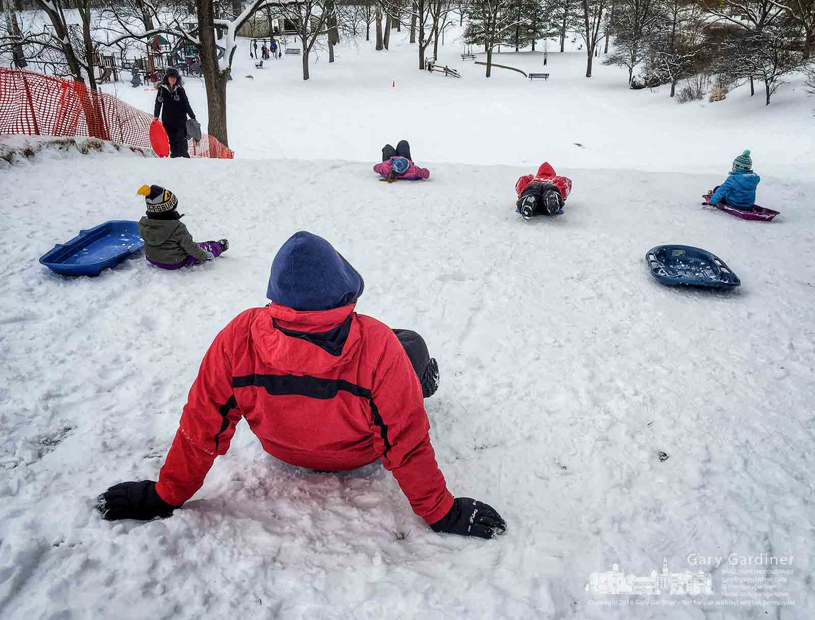 Families gather at the top of the sledding hills at Alum Creek Park North after an overnight very wet snowfall covered the short hill making it perfect for kids. My Final Photo for Feb. 7, 2018.