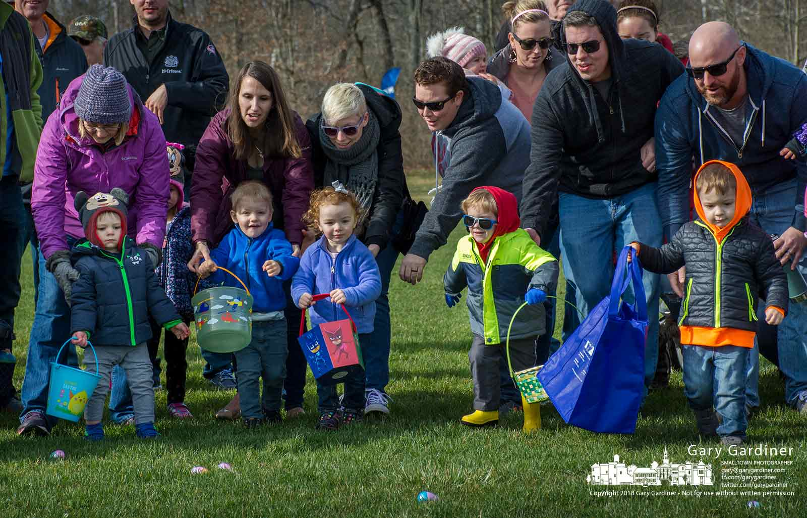 Parents release hold on their children at the start of one of the egg hunts at the city sports complex on Cleveland Ave. where 8,000 brightly colored eggs containing candy and toys disappeared into baskets and bags within about a minute after the starter's gun countdown. My Final Photo for March 31, 2018.