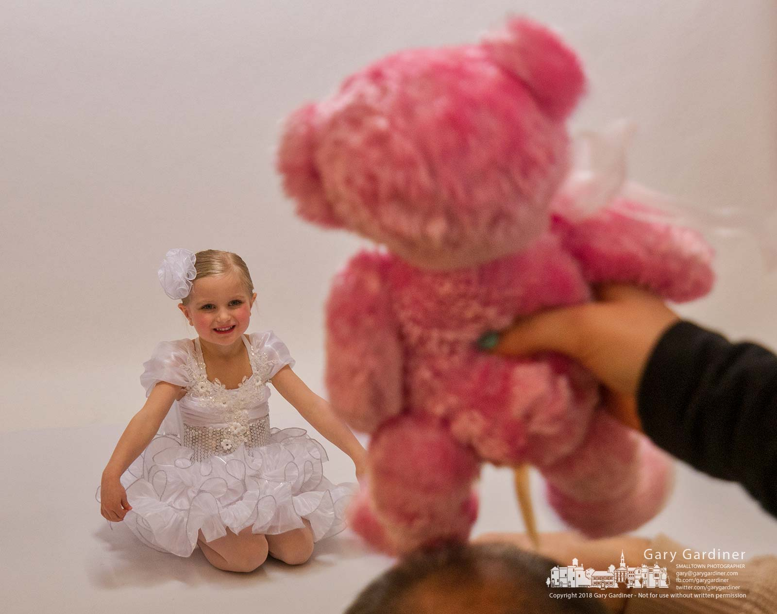 A Generations Performing Arts dancer smiles as instructed by the photographer's assistant and her pink bear during the annual photo shoot at the studio. My Final Photo for March 8, 2018.