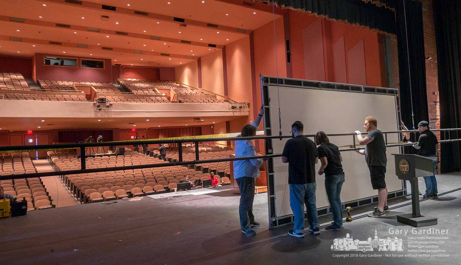 Stagehands attach a screen to rigging on the stage at Fritsche Hall at Otterbein University where Ohio Gov. John Kasich will give his final State of the State speech Tuesday. My Final Photo for March 5, 2018.