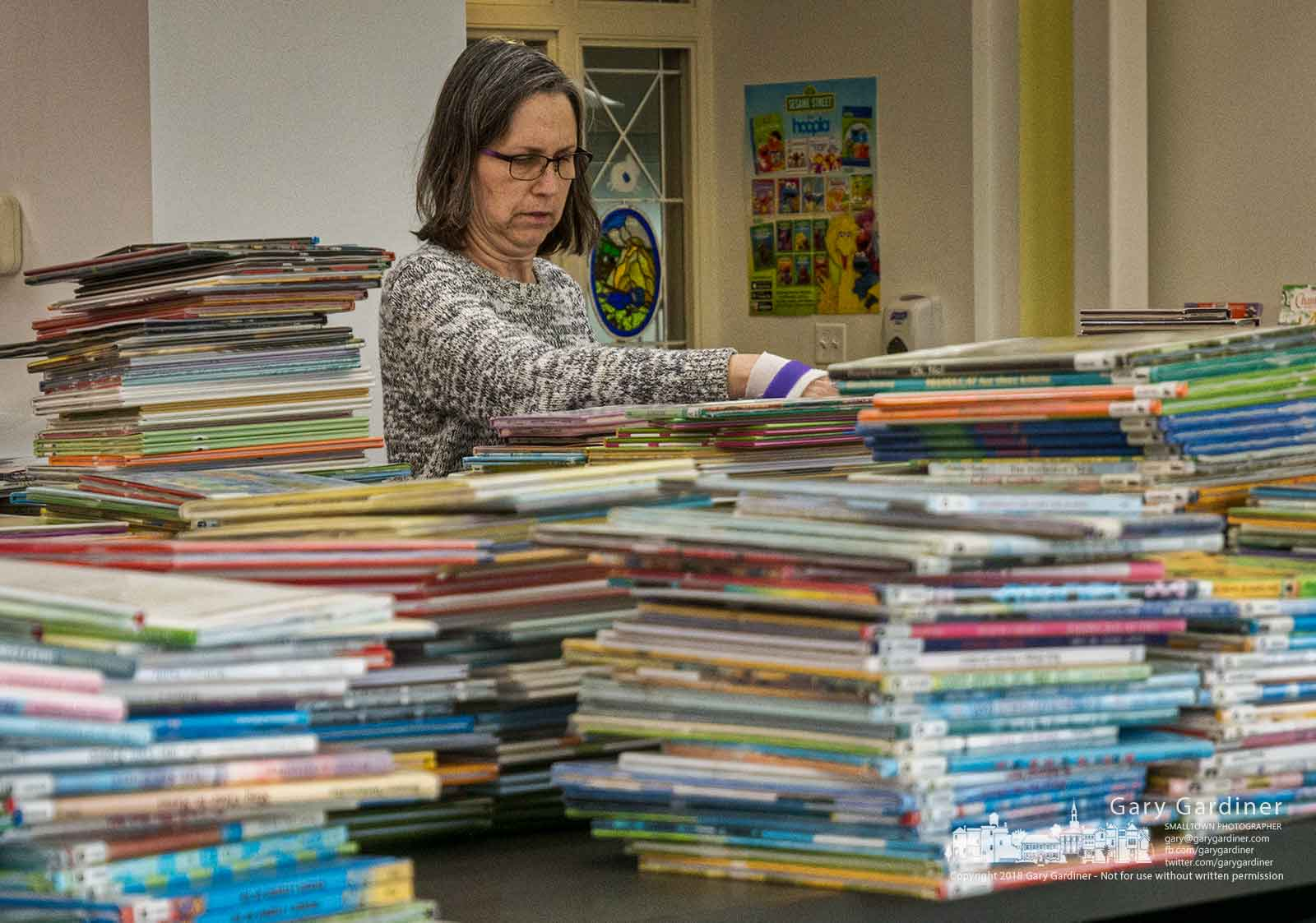 A librarian sorts through some of the books damaged by an overnight leak from a broken water heater at the Westerville Public Library. My Final Photo for March 16, 2018.