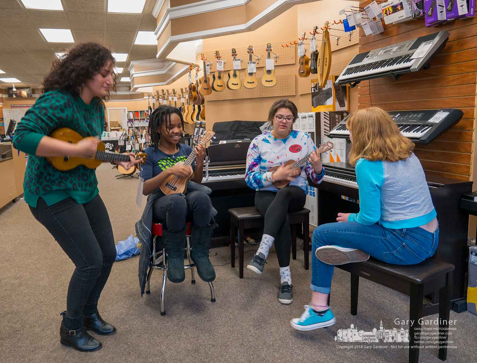 A trio of musicians gets an impromptu ukulele lesson from an instructor at Music & Arts in Uptown as one of them waits for her instructor to finish an earlier lesson. My Final Photo for March 29, 2018.