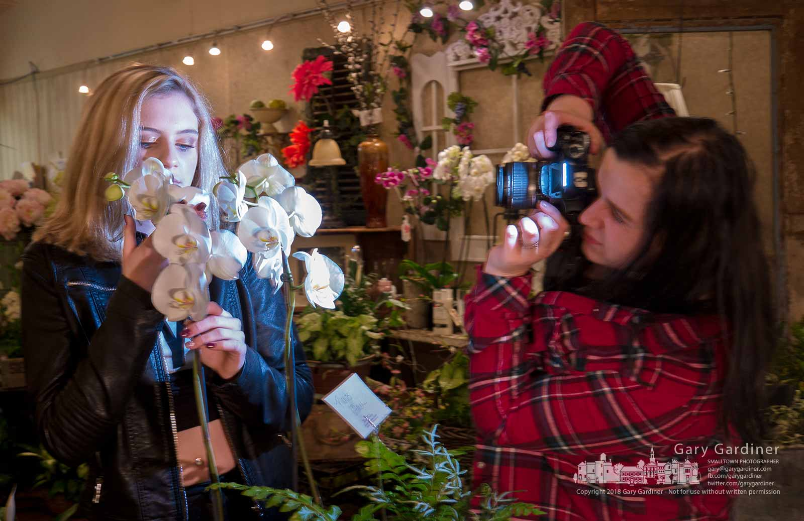 A photographer's flash illuminates her model posing among orchids on display in Talbott's Flowers in Uptown Westerville. My Final Photo for March 27, 2018.