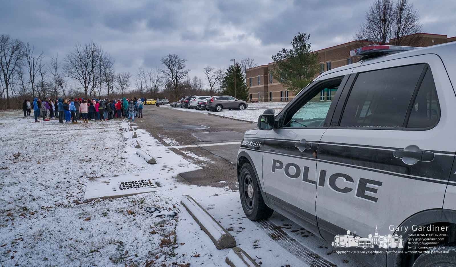 A Westerville police officer sits at the entrance to Heritage Middle School during a walkout by the students to express solidarity with a national movement to mark the one-month anniversary of the shooting incident at Marjory Stoneman Douglas High School in Parkland, Florida, where 17 people were killed and 14 others were injured. My Final Photo for March 14, 2018.