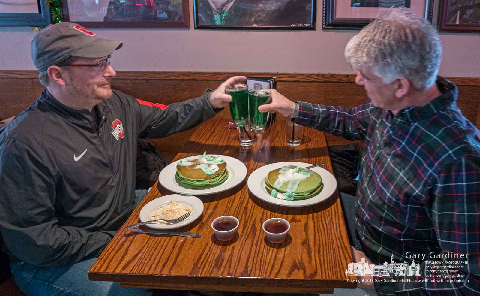 Two customers celebrating St. Patrick's Day salute the day by tapping beer glasses filled with green beer before eating green pancakes covered in green butter at Jimmy V's in Uptown Westerville. My Final Photo for March 17, 2018.