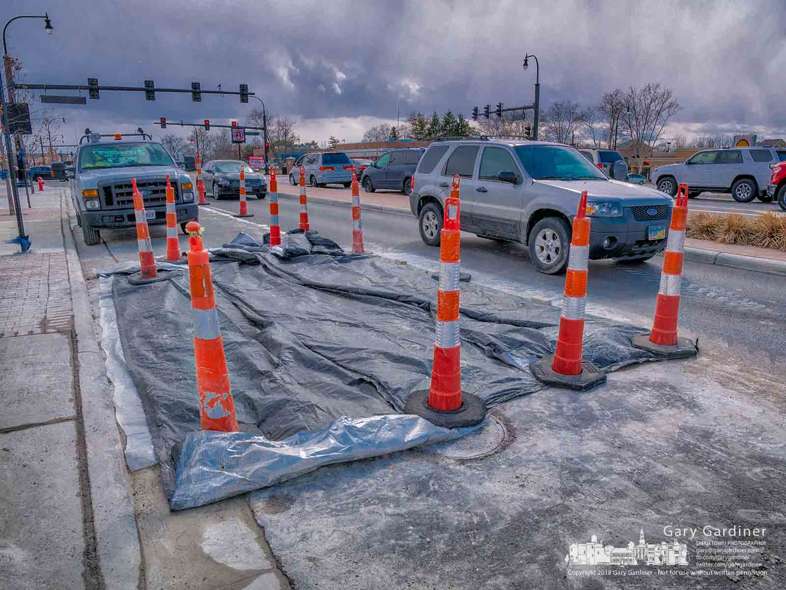 A Karvo Construction crew waits as a decision is made about how much longer to wait before removing traffic cones and a tarp covering concrete laid earlier in the day to repair a section of the pad for a bus stop at the corner of State and Schrock. My Final Photo for March 13, 2018.