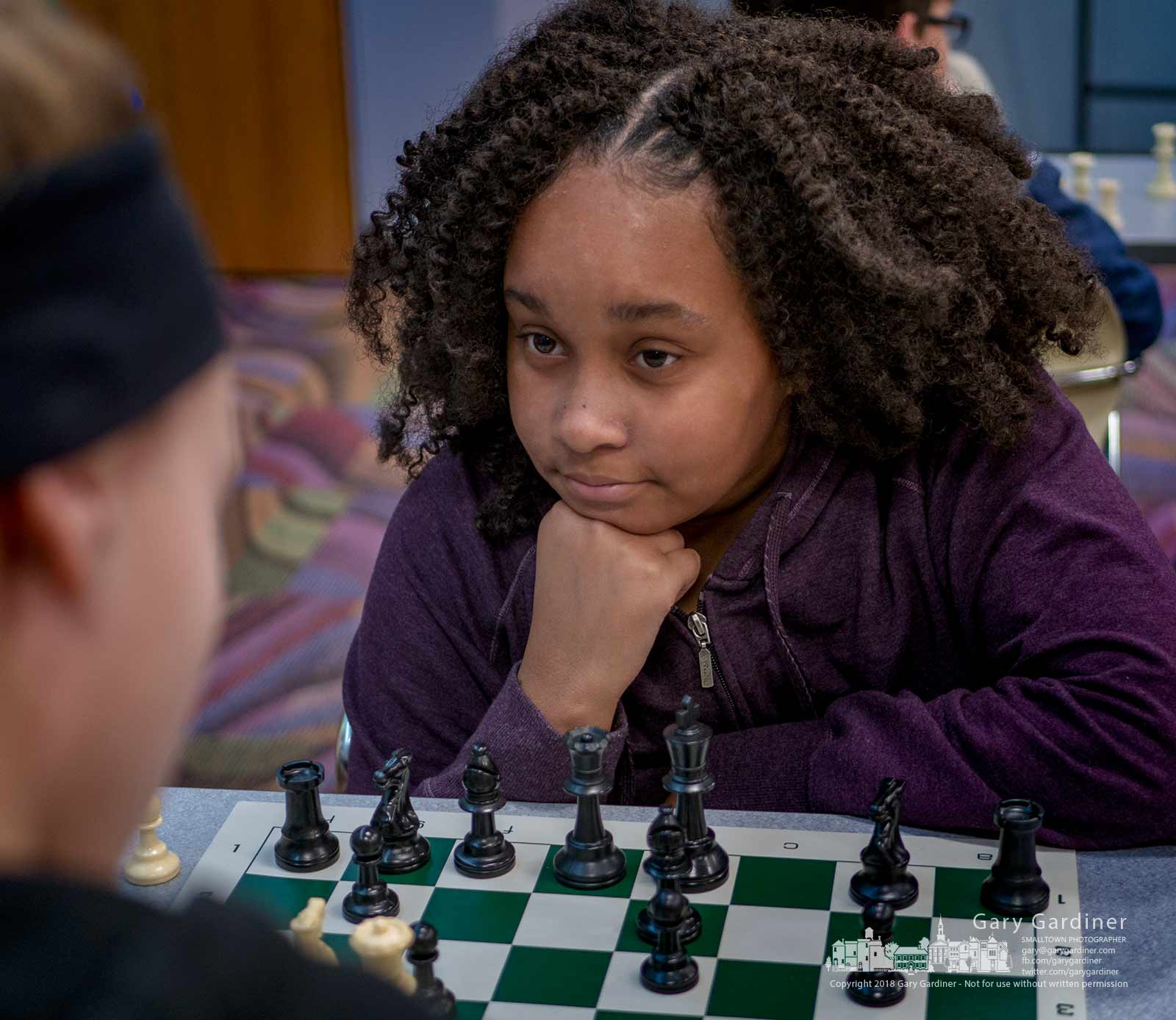 Jordan Hogans studies her chess opponent after making her move during a chess club meeting at the Westerville Public Library. My Final Photo for April 14, 2018.