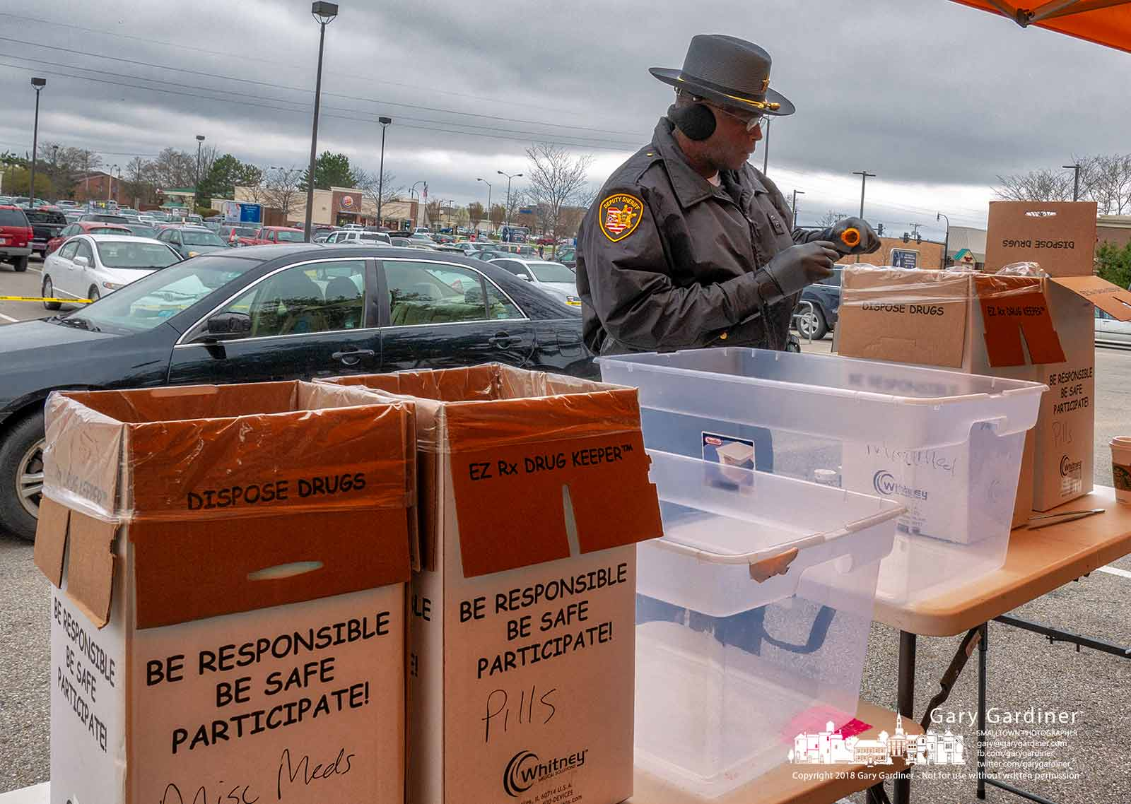 A Franklin County Deputy Sheriff sorts through bottles of drugs collected at a dropoff point in the Kroger parking lot as part of National Prescription Drug Take Back Day to dispose of prescription drugs. My Final Photo for April 28, 2018.