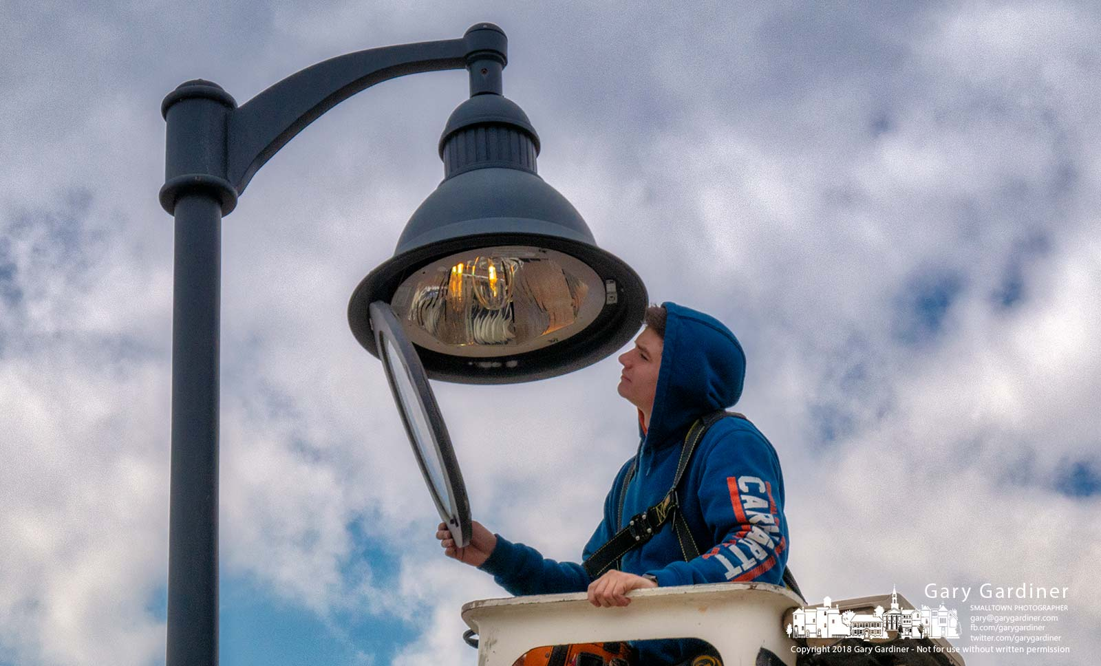 An electrician inspects repairs on a light over the picnic tables at Westerville Square. My Final Photo for April 10, 2018.