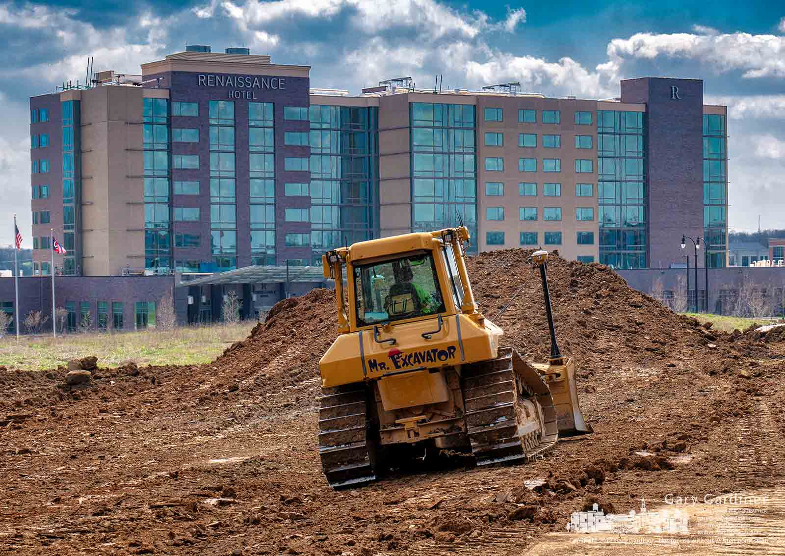 An excavating crew clears ground across the street from the Renaissance Hotel to make way for the construction of an office building. My Final Photo for April 26, 2018.