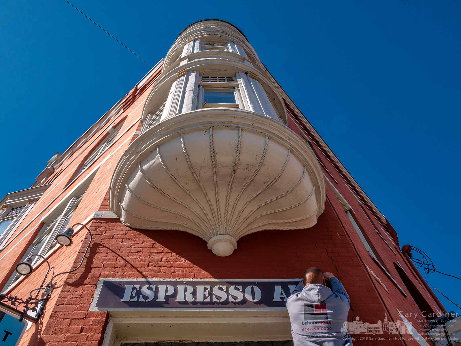 "A sign maker attaches the new ""Espresso Air"" sign over the doorway of the coffee shop at the corner of State and Main in the Holmes Hotel as the new owners complete another step of their renovation of the popular location. My Final Photo for April 20, 2018."
