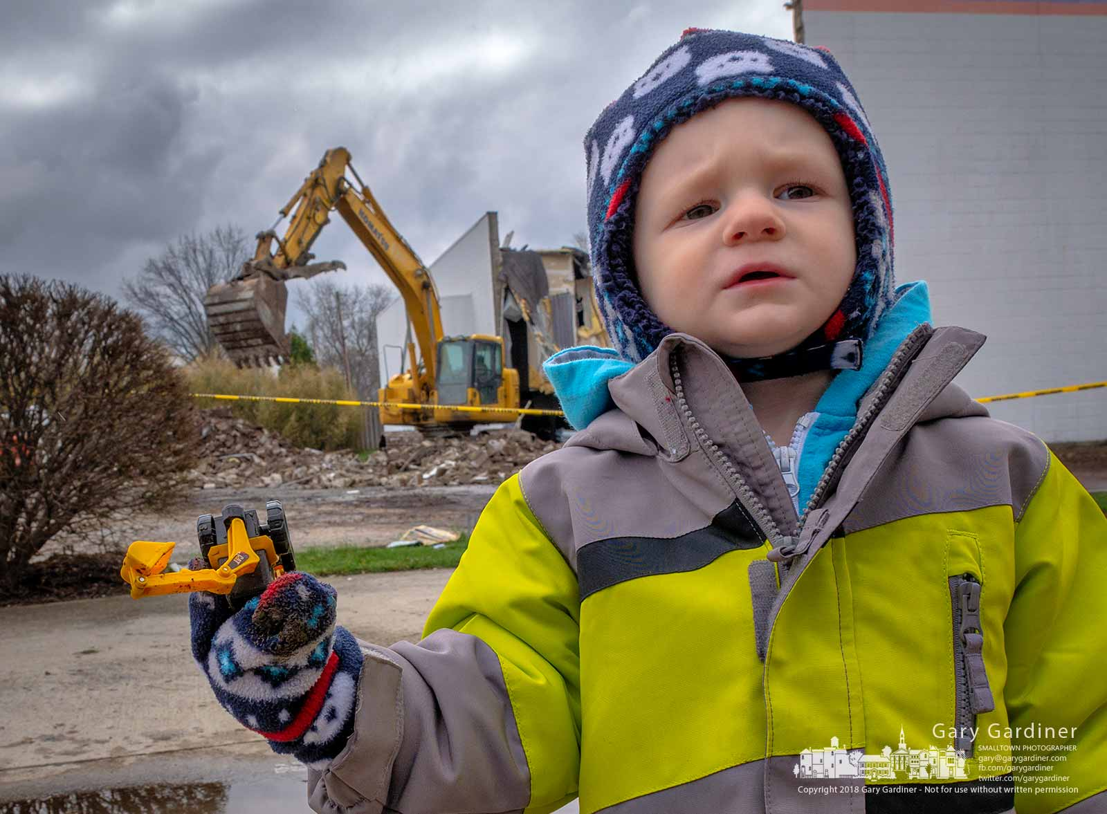 Three-year-old Drew shows off the plastic replica of the same equipment being used to demolish the Hollywood Cinema Theaters as workers began removing the building to make way for a new Aldi store. My Final Photo for April 19, 2018.