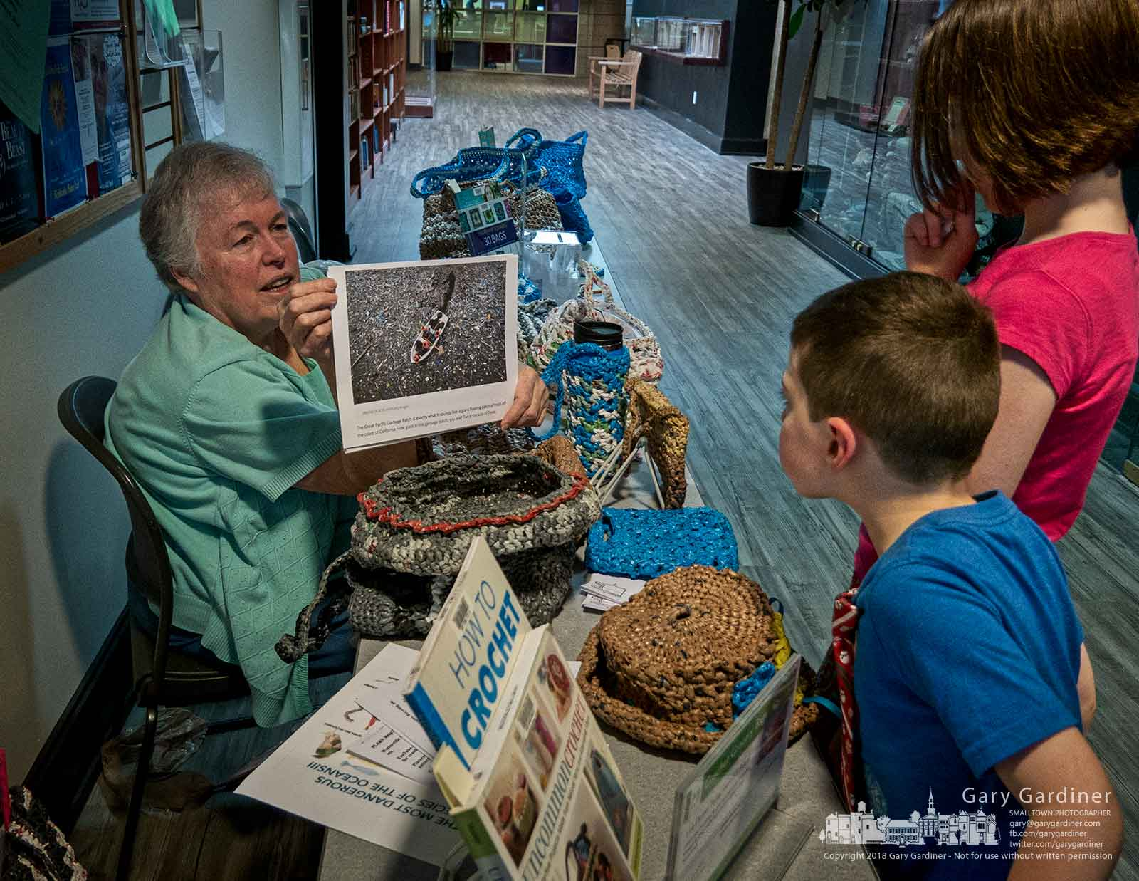 Rose Blanchard shows a photo of a boat traveling through a floating island of plastic as she explains her crocheting process that turns discarded plastic bags into shopping bags to a family at the Westerville Public Library on Earth Day. My Final Photo for April 22, 2018.
