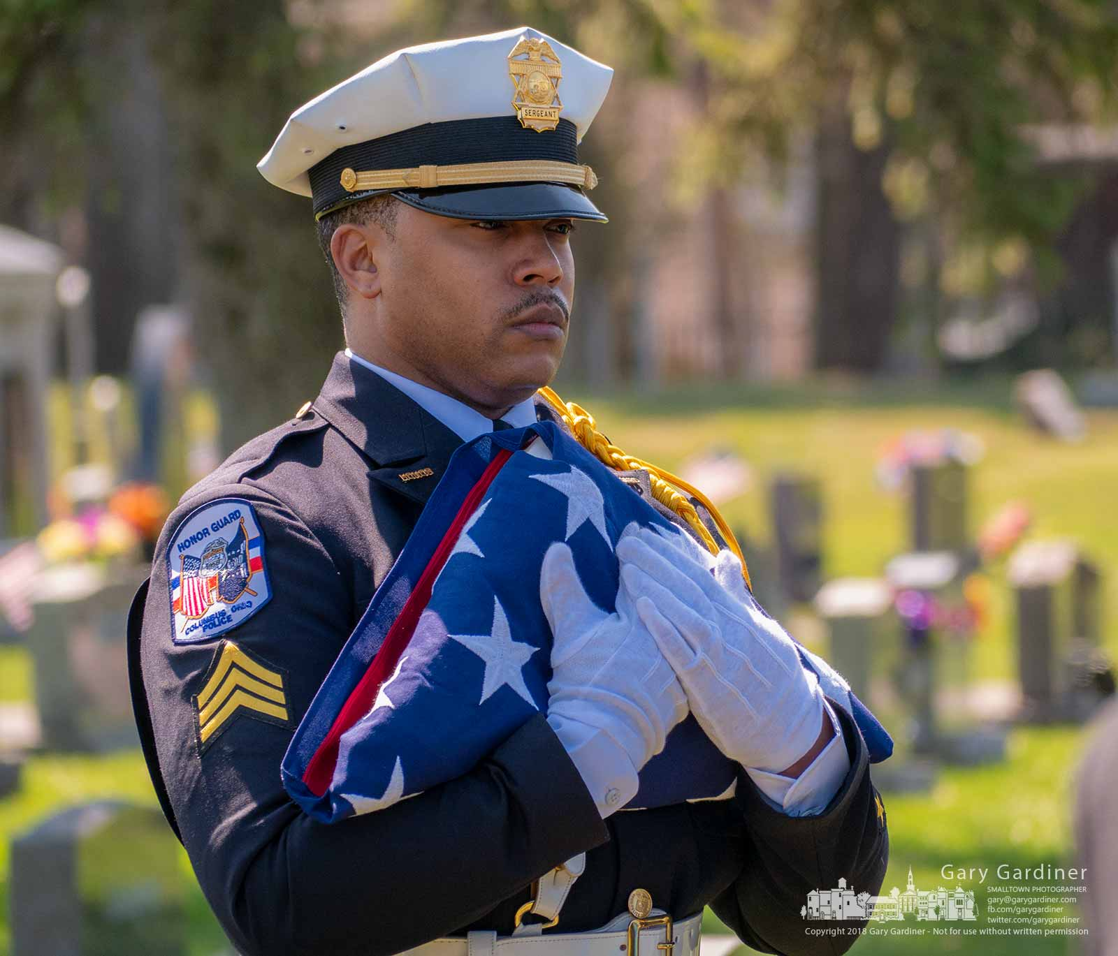 A Columbus Police Honor Guard officer carries a folded flag to present it to the family of a retired officer who was buried Thursday at Blendon Central Cemetery. My Final Photo for April 5, 2018.