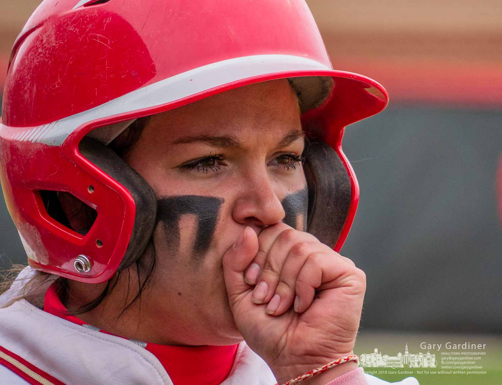 An Otterbein University softballer blowsinto her hand as she waits in the batters box in the second game of a doubleheader against Marietta Friday afternoon. My Final Photo for April6, 2018.