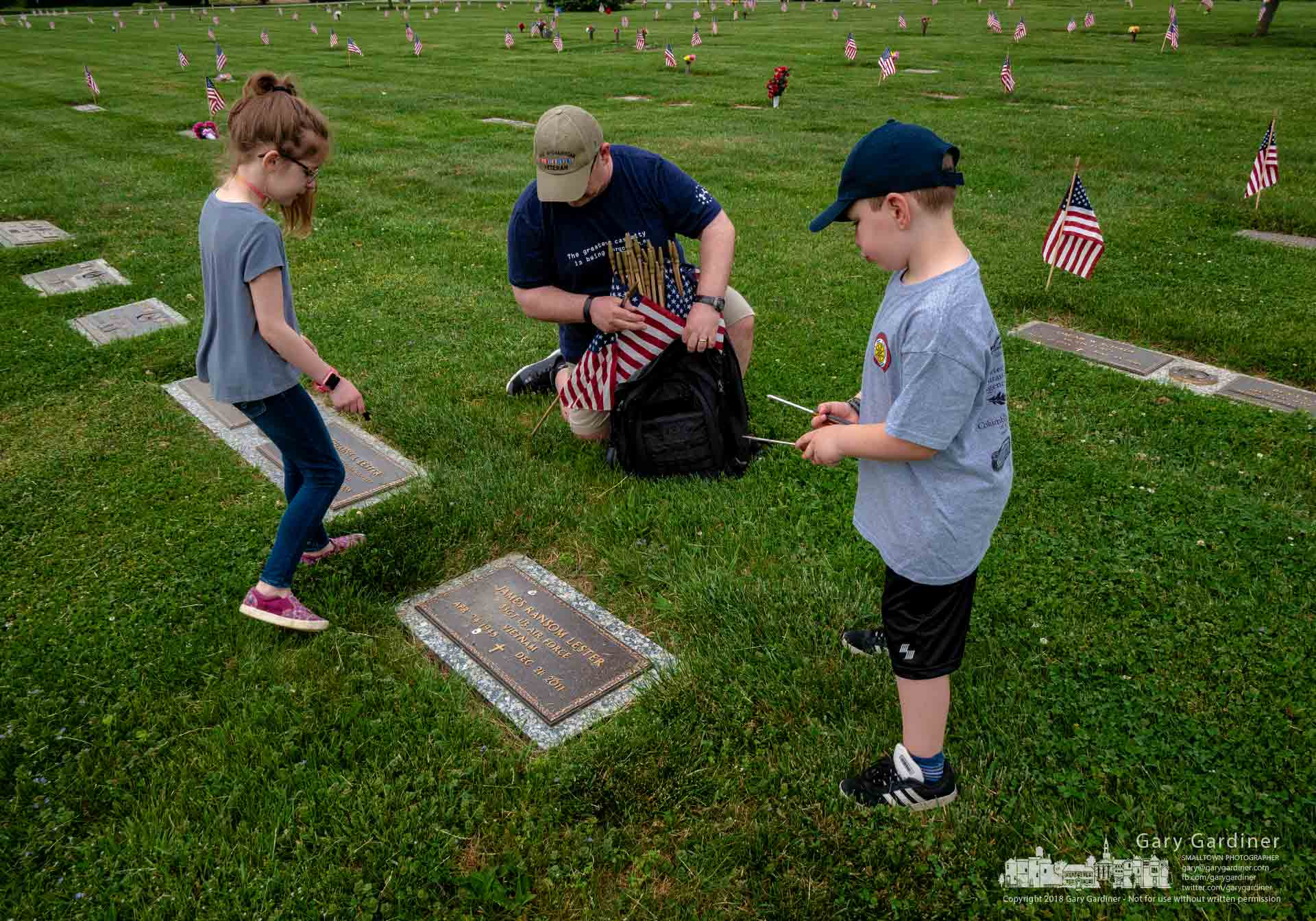 Retired Army veteran David Troutman, his two children, and members of the American Legion Post place American flags on the graves of veterans at North Lawn Cemetery in Westerville in preparation for Memorial Day Monday. My Final Photo for May 26, 2018.