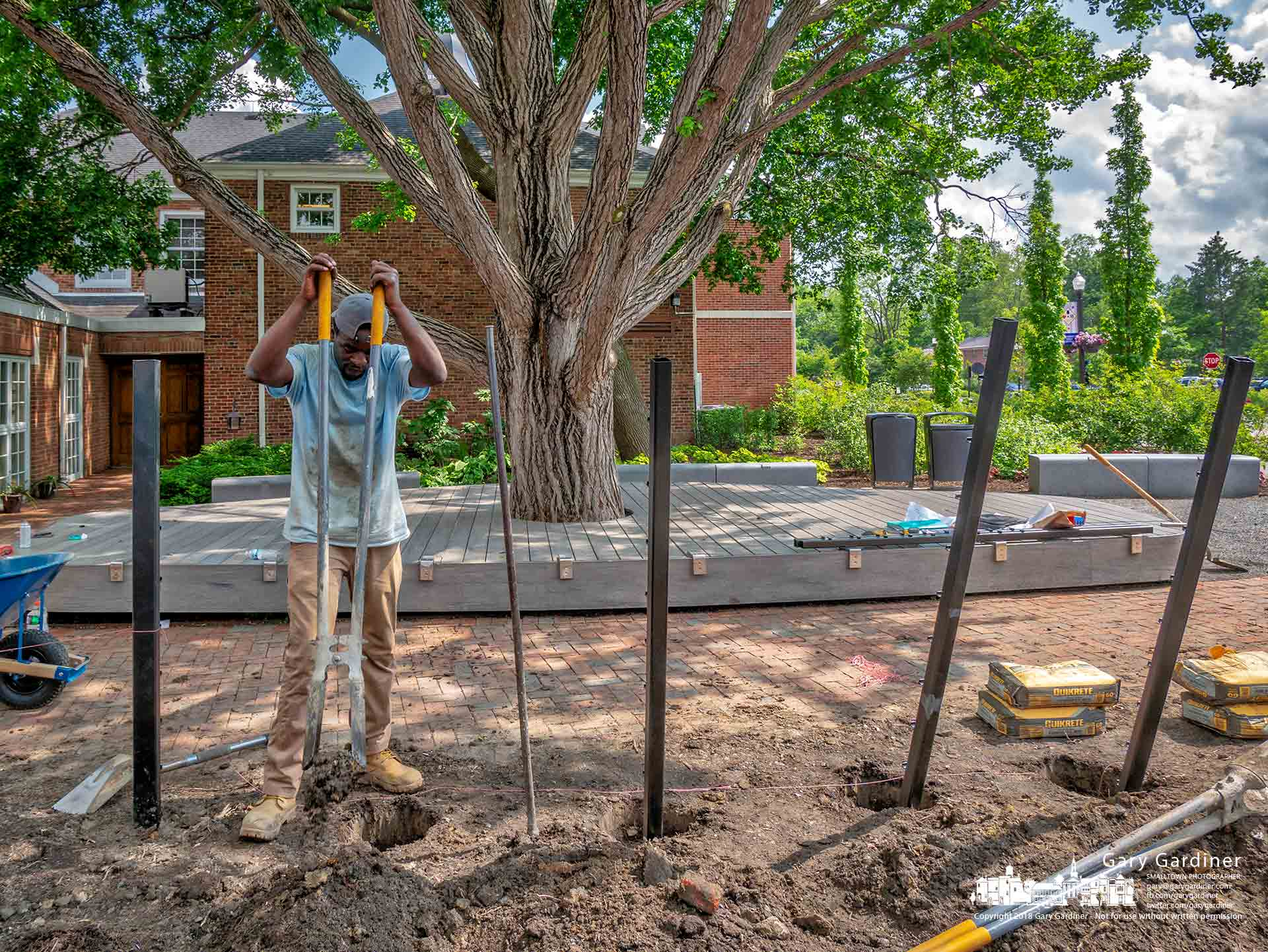A worker uses a post hole digger to excavate for a new fence to be built along the northern edge of city hall and the newly renovated walkway and seating area. My Final Photo for May 22, 2018.