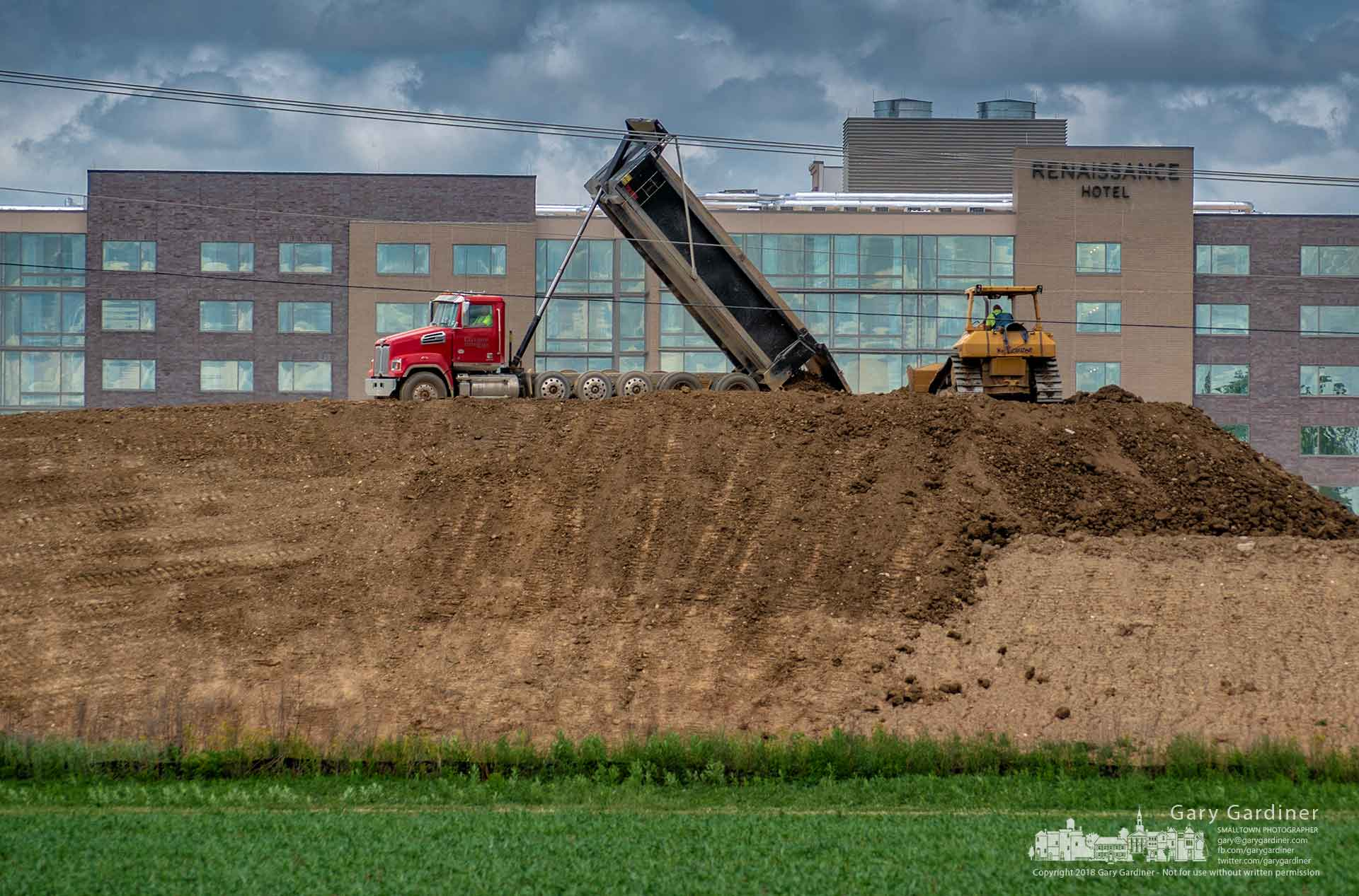 A truck dumps another load onto a farm field being temporarily used to store dirt removed from an office building construction project across from the Renaissance Hotel in Westerville. My Final Photo for May 31, 2018.