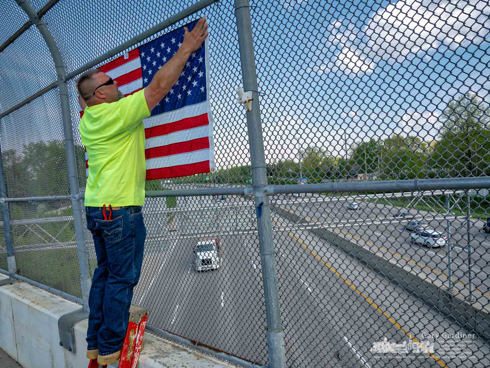 Blendon Township workers replace flags on the chain link fence bordering the Dempsey Road Bridge over I-270 as part of the township's spring cleanup before Memorial Day. My Final Photo for May 9, 2018.
